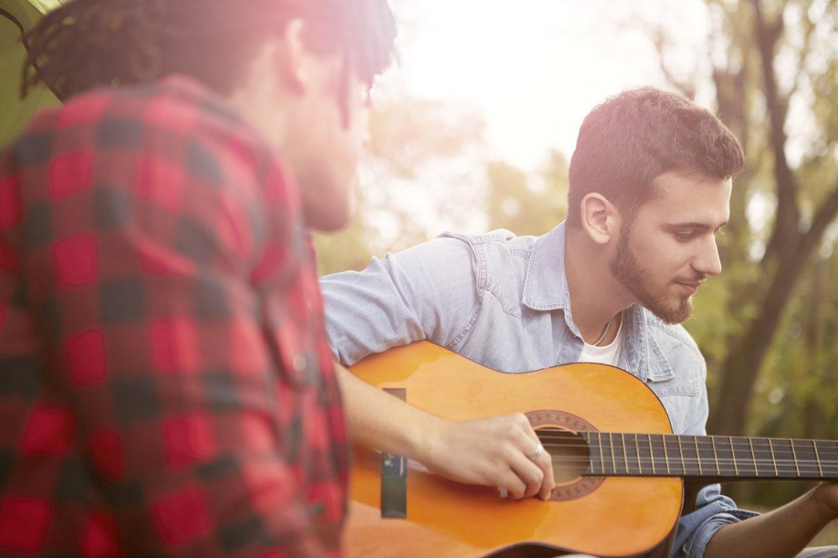 a man teaching guitar
