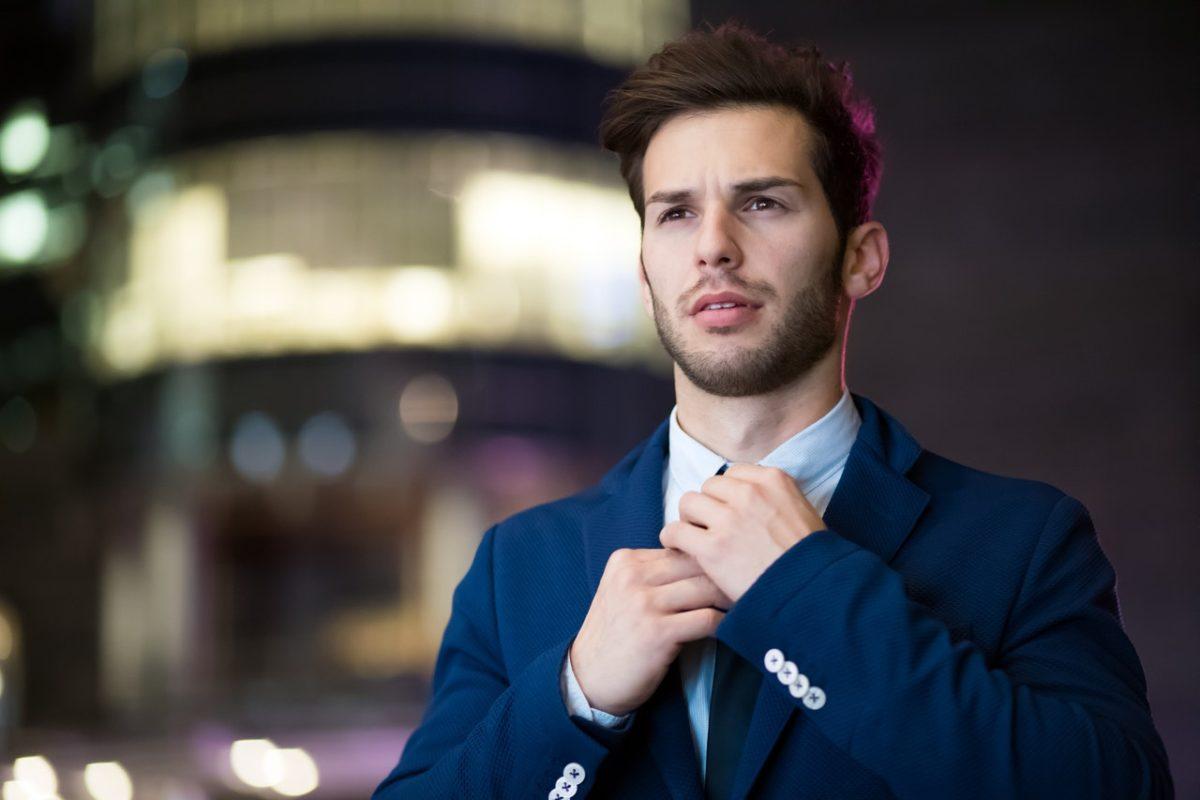 a man adjusting their tie