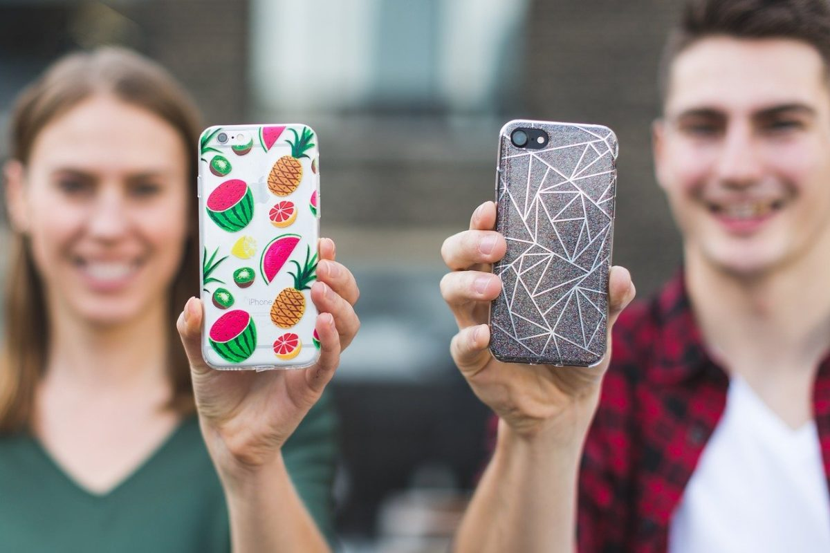 two people holding their phones up/Best Products to Sell to College Students