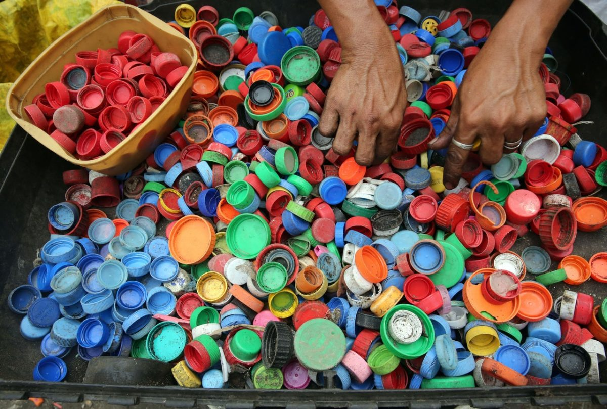a person sorting bottle tops