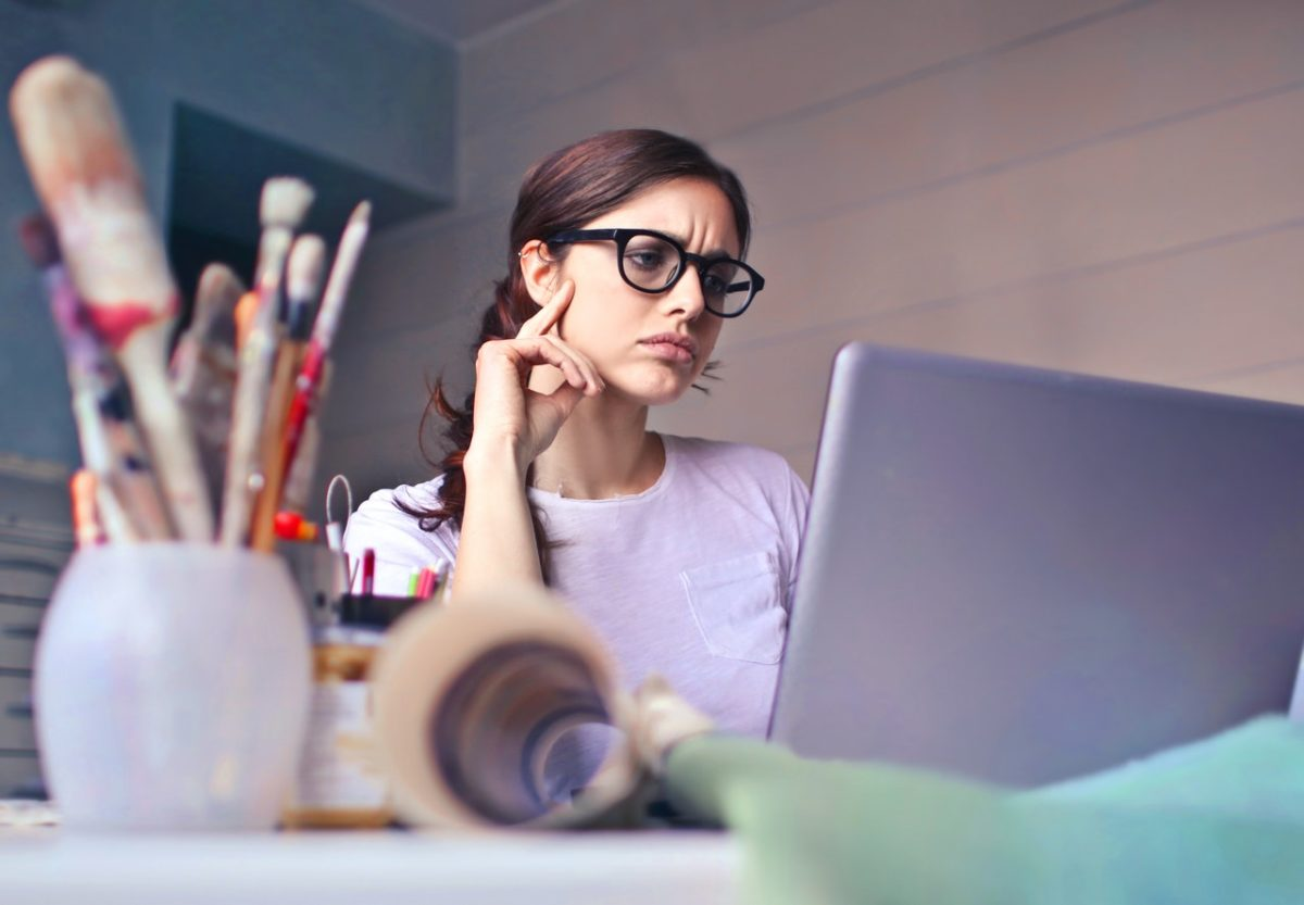 A woman studying on a laptop/How to Start a Retreat Business